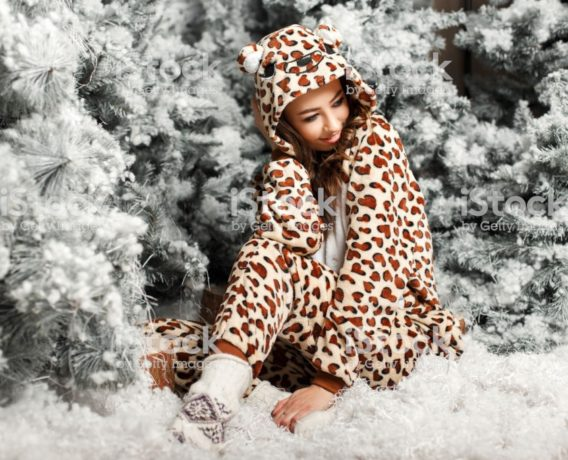 Happy cute girl in a trendy bear pajamas sitting near a Christmas tree